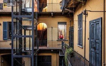 """تعيش """"ريبيكا كاسالي"""" في هذا المجمع السكني الذي كان يضج بالحياة ليلًا في ميلانو، فاستسلم اليوم للسكون بسبب الحجر المنزلي. تقول كاسالي: """"أعاني الوحدة كثيرًا. فالسكون والأماكن الفارغة تجعل كل شيء سرياليًا""""."""