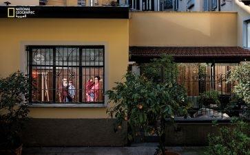 """""""لوكا فولتا"""" يحمل ابنه """"جيوفاني"""" (4 أعوام) و""""ميكاييلا كروسي"""" تحمل ابنتهما """"أغاتا"""" (6 أعوام) في غرفة الأطفال. يقول الوالدان إنهما يحاولان شغل نفسيهما بالألعاب."""