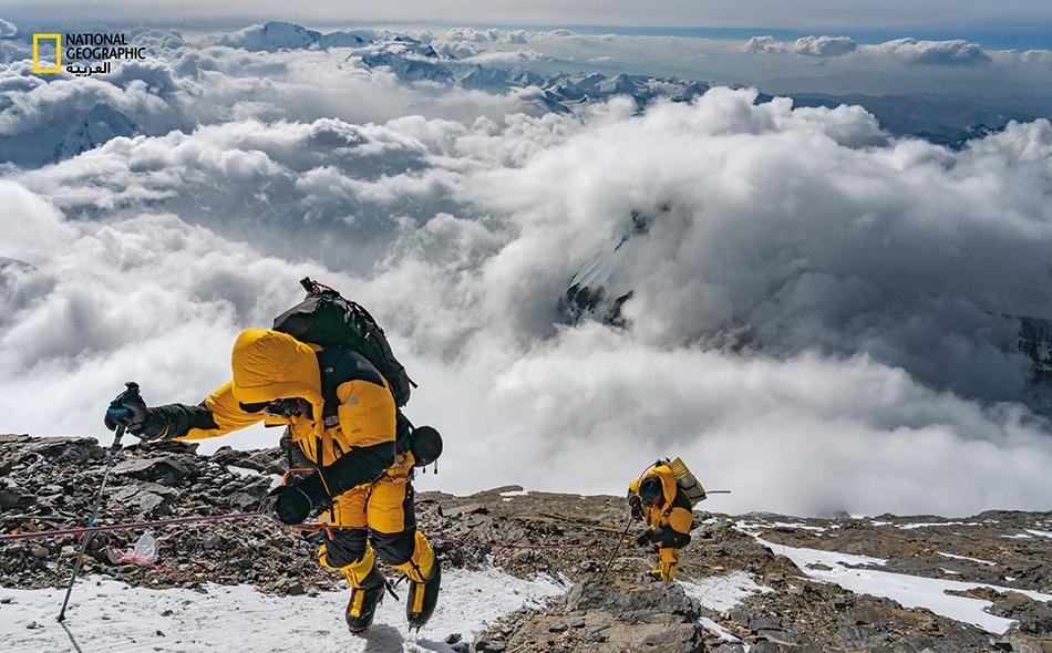 """أثناء سحب """"أُرفاينغ"""" (الظاهر إلى اليسار) و""""سينوت"""" أنفاسا عميقة من قناعي الأوكسجين في ما يسمّى """"منطقة الموت""""، يتّبع الرجلان حبلًا ثابتا إلى """"الحافة الشمالية الشرقية"""" لجبل إيفرست عند ارتفاع نحو 8300 متر؛ وهو ارتفاع أعلى من جميع جبال العالم ما عدا خمسة."""