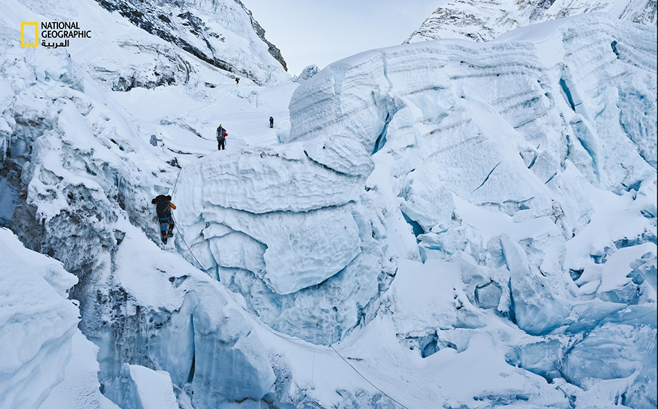 """من أجل صعود """"منحدر خومبو الجليدي""""، يجب على متسلقي الجبال سلك مسار محفوف بالمخاطر تتخلله تشكيلات متحركة من الجليد. ويعتمد المتسلقون على الأحذية المسمارية المربوطة بأقدامهم ويتبعون مسارًا من الحبال الثابتة التي يمدها أدلّاء """"الشيربا"""" المحنّكون. الصورة:..."""