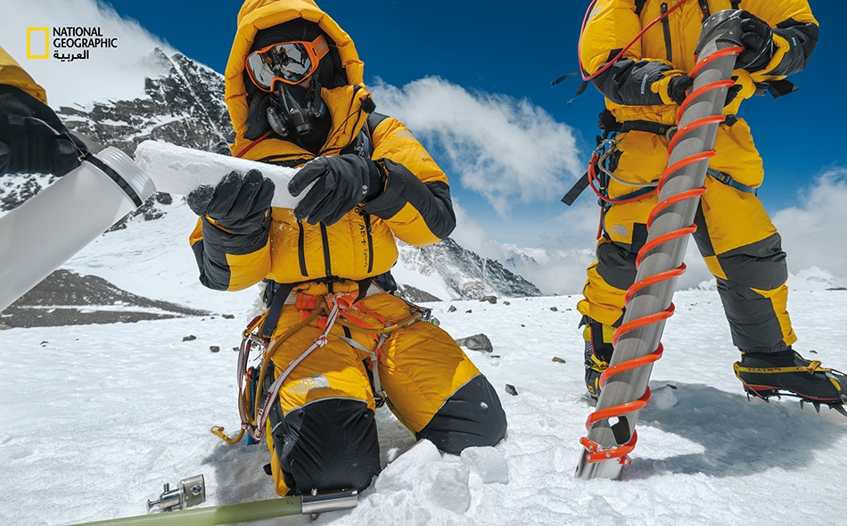 """استخدم عالم المناخ """"ماريوس بوتوكي"""" (الجالس إلى يمين رفيقه) مثقابًا خاصًا لأخذ عينة أساسية من الجليد على ارتفاع 7925 مترًا عند """"الفج الجنوبي"""" في إيفرست. وقام فريقه فيما بعد بنقل نحو 14 كيلوجرامًا من عينات الجليد إلى أسفل الجبل. وتحوي طبقات الجليد..."""