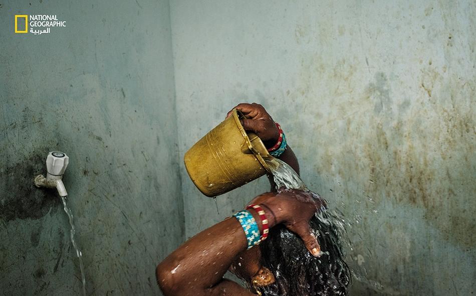 """امرأة تستحم غير بعيد عن مدينة """"بوبانيشوار"""" بولاية أوديشا في شرق الهند. يفتقر جل العائلات الحضرية في الهند -و 82 بالمئة من العائلات الريفية- إلى مياه الأنابيب. الصورة: Andrea Bruce"""