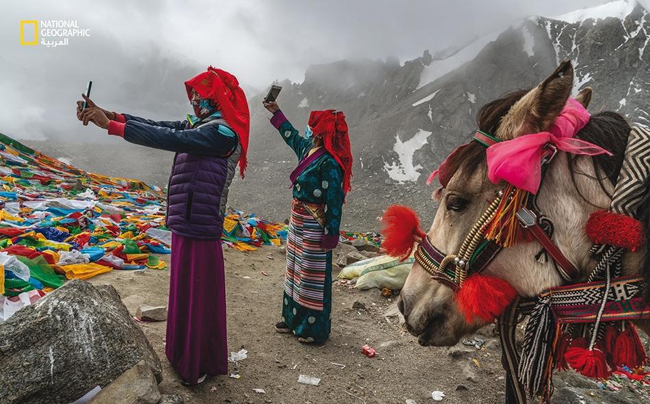 """الصين، تلتقط حاجّتان صور """"سيلفي"""" في شهر سبتمبر في """"درولما لا""""، أعلى نقطة في الطواف المعروف باسم """"كورا"""". تبلغ مسافة هذا الطواف 52 كيلومترًا، وهو جولة دائرية تأملية حول جبل """"كانغرينبوك"""" في التيبت."""