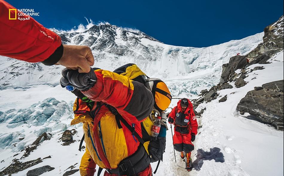 """المصور """"رينان أوزتورك"""" يتبادل التحية مع متسلّق جبالٍ عائد إلى """"مخيّم الانطلاق المتقدّم""""."""