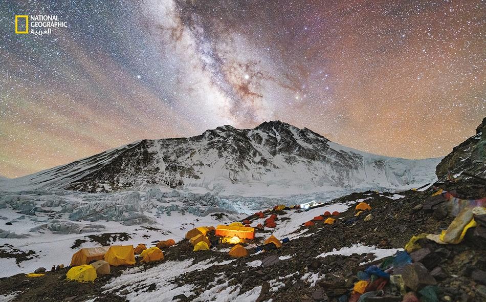 """من """"مخيّم الانطلاق المتقدّم""""، حيث يفترش الأرضَ أكثرُ من 200 شخص على نصف كيلومتر من الركام الجليدي، لا يبدو """"سقف العالم"""" أقرب إلينا من مجرّة درب التبانة. أما قمة إيفرست فهي تلك الذروة في أقصى اليمين، التي بالكاد تُرى من خلف """"الفجّ الشمالي"""" (الظاهر إلى..."""