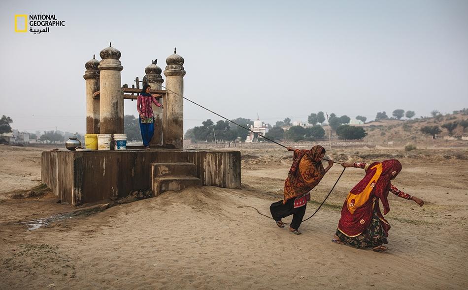 """تكدّ النساء لجلب المياه الثمينة من بئر في """"دونغرا"""" بإقليم راجستان الصحراوي. وقد حلت آبار كهذه محل الهياكل المتدرجة القديمة، حيث كانت النساء تُضطر للهبوط في سلالم من مئات الدرجات للوصول إلى موقع المياه الجوفية."""