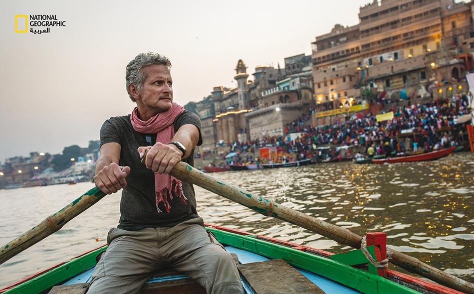 """يجدّف الكاتب """"بول سالوبيك"""" على طول جزء من نهر الغانج في فاراناسي، أقدس مدينة هندوسية. على الرغم من أن الماء العكر ههنا يحمل رماد زُهاء 30 ألف شخص ممن تُحرَق جثثهم كل عام، يعتقد المؤمنون بتلك العقيدة أنه نقي بما يكفي للشرب."""