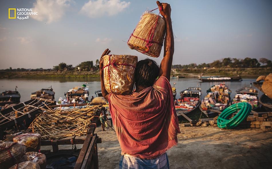 """يُوصل عاملٌ البضائعَ إلى قوارب ستنقلها إلى قرى على طول نهر """"براهمابوترا""""."""