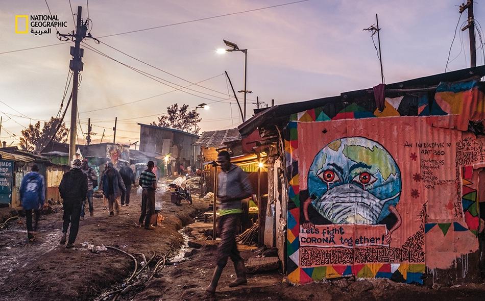 """لوحة جدارية رُسمَت على جانب كُشك في حي """"كيبيرا"""" الفقير في نيروبي، وقد كُتب عليها """"لنحارب كورونا معًا!"""". يَصعب تطبيق تدابير الحجر المنزلي والتباعد الجسدي في هذه المجتمعات المحلية حيث يعيش مئات الآلاف من الناس في أماكن متقاربة، ويعتمد بعضهم على بعض في..."""