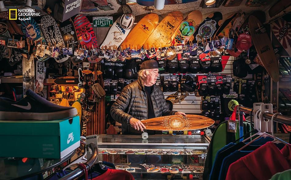 """يُعد متجر """"ريب سيتي سكيتس"""" في سانتا مونيكا أيقونة لدى ممارسي التزلج اللوحي على الصعيد العالمي، وقد بدأ في طرح مستلزمات هذه الرياضة منذ عام 1978. يقول مالك المتجر بالتشارك، """"جيم ماك دويل"""" (الظاهر في الصورة): """"في كثير من الأحيان، يأتي الأطفال إلى هذا..."""