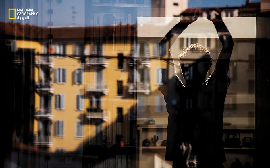 """ميلانو، إيطاليا. كانت إيطاليا، بوصفها من أوائل بؤر """"كوفيد-19″، أول دولة أوروبية تفرض حجرًا منزليًا شبه تام. تلاحظ المصورة الفوتوغرافية، """"كاميلا فيراري""""، رفقة شريكها تمازجَ صور المباني في الخارج مع المشاهد داخل شقتهما. الصورة: Camilla Ferrari"""