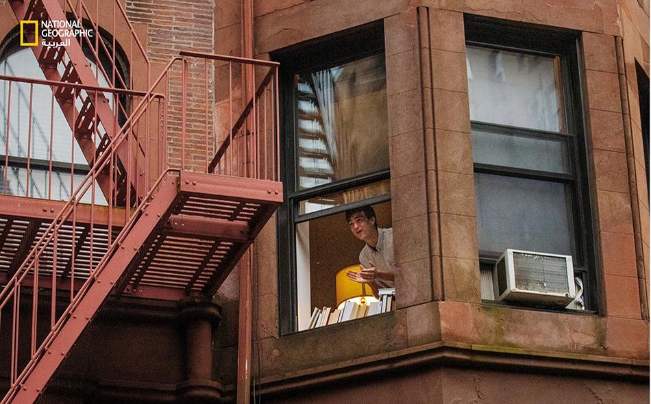 """مدينة نيويورك: اتخذ المصور البنغالي، """"إسماعيل فردوس""""، القرارَ الصعب بالبقاء في مدينته ليوثق لبعض اللحظات، كهذه التي يطل فيها رجلٌ من نافذة شقته. الصورة: Ismail Ferdous"""