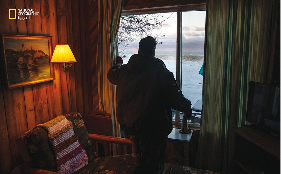 """8 فبراير 2020 – بحيرة هورون: في """"أوسكودا"""" بولاية ميشيغان، تَدرس """"إيلينا ماك كينزي"""" بحيرة هورون من أحد المنازل التي تستأجرها لقضاء إجازاتها. عادة ما تحمي ألواح الجليد السميكة حول البحيرة الشاطئَ ضد العواصف. لكن فصل الشتاء الماضي كان دافئًا، وتسببت..."""